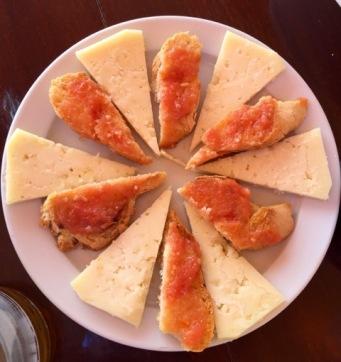 Den perfekta tapas-tallriken. Manchegoost och tomat och vitlöksröra på bröd.